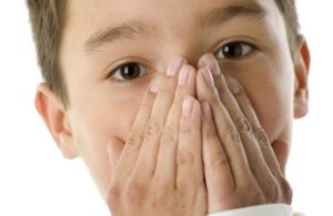 boy covering mouth with two hands